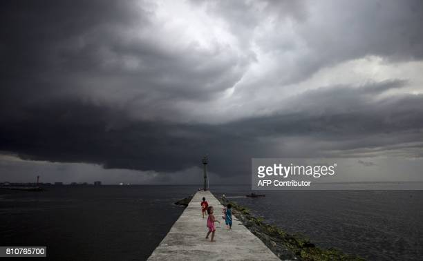 Filipino children play at the breakwater as rain clouds approach in Baseco Tondo on July 8 2017 / AFP PHOTO / NOEL CELIS
