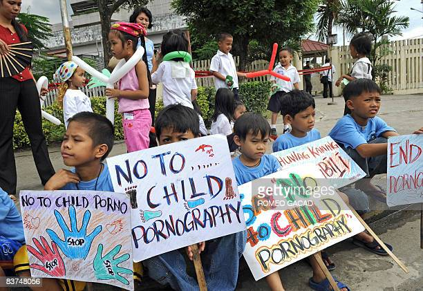 Filipino children rally together with their parents and hold placards during an antichild pornography demonstration outside the Senate in Manila on...