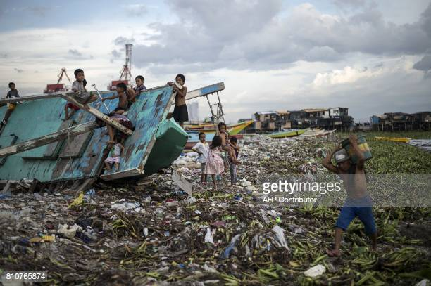 Filipino children rest at a broken fishing boat in the garbage filled Manila Bay in Baseco Tondo on July 8 2017 / AFP PHOTO / NOEL CELIS