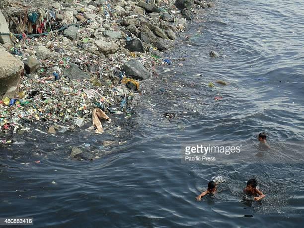 Filipino children swim along the dirty breakwater of Manila Bay in Navotas City north of Manila Philippines