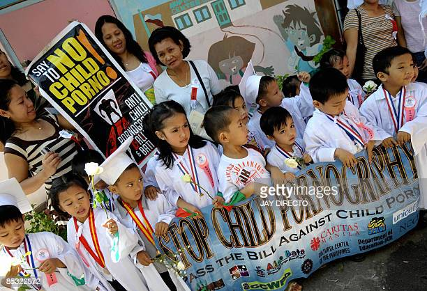Filipino children walk together with their parents during an antichild pornography protest march from an auditorium to the daycare center inside the...