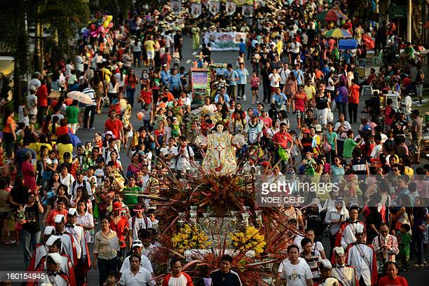 Filipino christian devotees display their religious icons of the baby Jesus Christ during the annual Grand Santo Nino Procession in Manila on January...