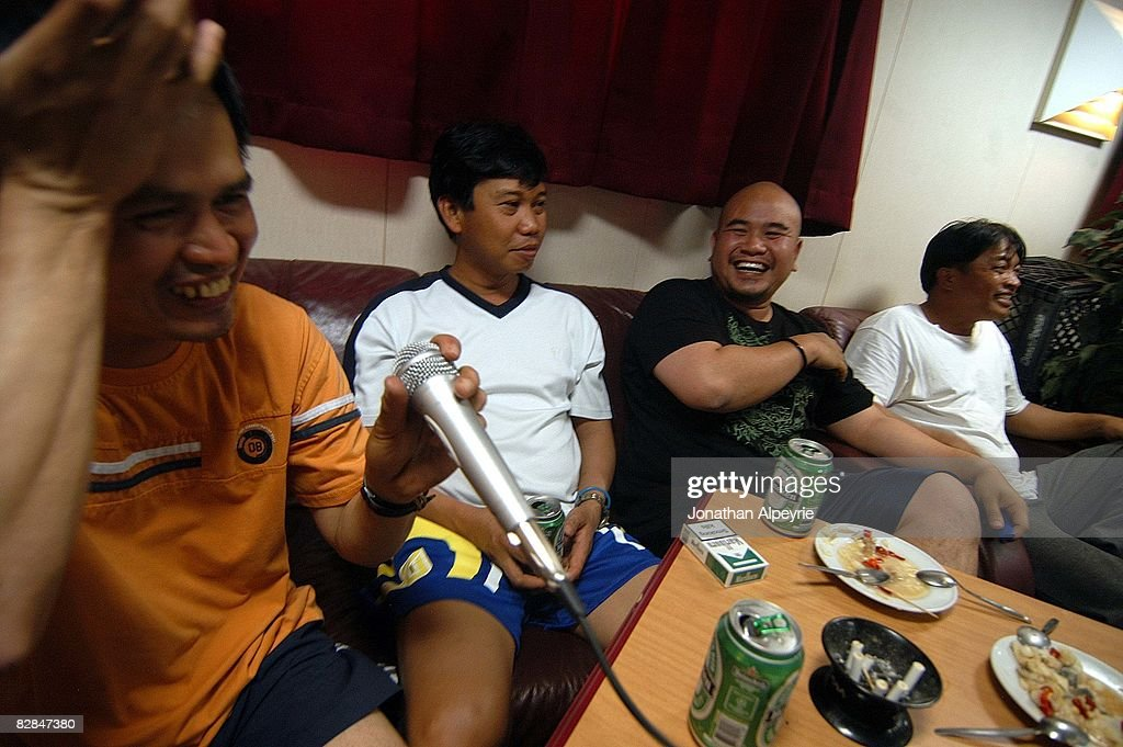 Filipino crewmen are hainvg a good time during a late night Karaoke session, on July 19, 2008, in France. beer is allowed on the tanker. The Joe tanker company is one of the last ones allowing liquor on board.