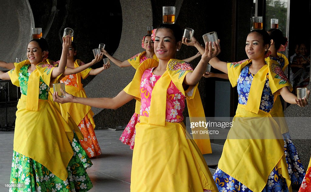 Filipino dancers perform the Binasuan, a dance using glasses with liquid, during the Pasinaya Festival in Manila on February 3, 2013. The Cultural Center of the Philippines held one day multi-arts festival as thousands of artists from dance, music, theater, visual arts, literature and cinema took part in the festivities. AFP PHOTO / Jay DIRECTO