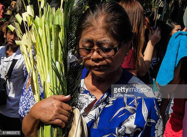 Filipino devotee carrying palm fronds during a mass at the Baclaran Church Palm Sunday marks the triumphant entry of Jesus Christ to Jerusalem...