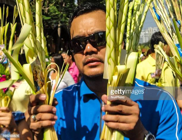 Filipino devotees carrying palm fronds attend mass at the Baclaran Church in Paranaque City on Palm Sunday 20 March 2016 Palm Sunday marks the...