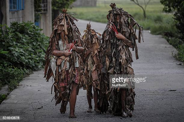 Filipino devotees covered in mud and dried leaves walk in a road in a pagan religious tradition to mark the 'Taong Putik' festival and the Feast of...