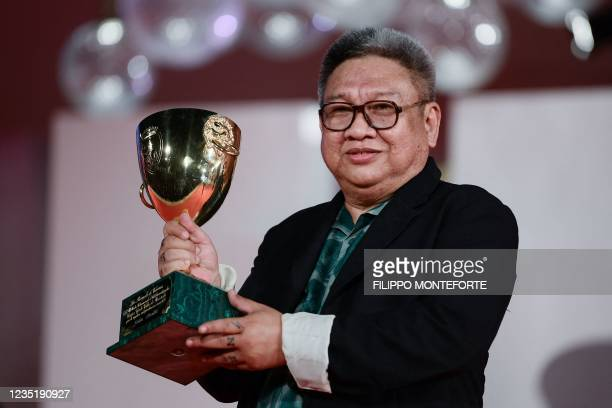 """Filipino director Erik Matti poses with the trophy he received on behalf of actor John Arcilla, the Coppa Volpi for Best Actor in """"On the Job: The..."""