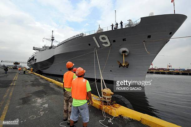 Filipino dock worker view the USS Blue Ridge the flagship of the US Seventh Fleet during the ship's arrival at Manila port on February 19 2009 The...