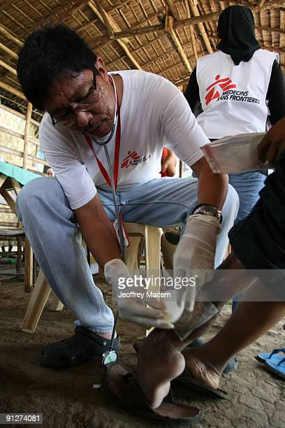 Filipino doctor Luis Jose Presbitero from Doctors Without Borders treats a patient inside evacuation camp on September 30 2009 in the southern...