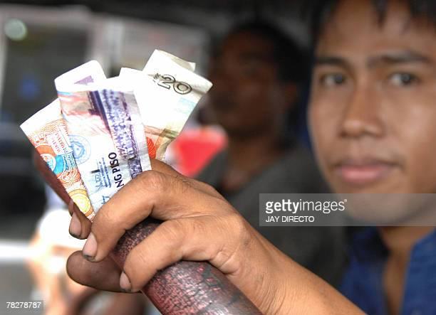 Filipino driver Michael Corpos holds Philippine peso bills in Manila 06 December 2007 The peso hit a fresh sevenandahalfyear high of 4185 pesos...