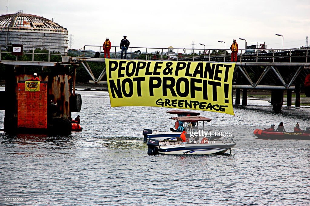 Filipino environmental activists unfurled a banner reading PEOPLE AND PLANET, NOT PROFIT from Shells Batangas oil refinery, sending a sharp reminder to Shell to attend upcoming hearing into the responsibility of big fossil fuel companies for climate-related human rights harms in Batangas Bay, Batangas City.