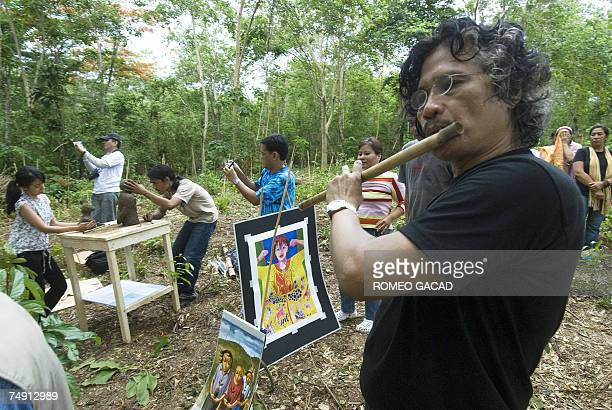 Filipino environmental artists Gus Albor plays a bamboo flute after the on the spot painting session during a massive tree planting drive in the...