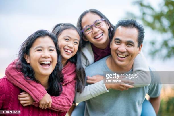 filipino family laughing piggyback portrait stock photo - filipino family stock pictures, royalty-free photos & images