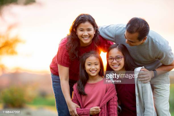 filipino family of four together at sunset - filipino family stock pictures, royalty-free photos & images