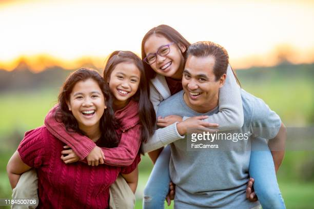 filipino family piggyback portrait outside stock photo - life insurance stock pictures, royalty-free photos & images