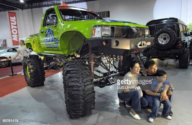 A Filipino family poses under a customized rock crawling truck at the opening of the fourday Manila Auto Salon at the SMX convention center in Manila...