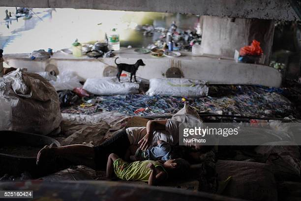 A Filipino family takes a siesta or afternoon rest under a busy bridge they use as a shelter in Paranaque suburban Manila Philippines January 24 2014...