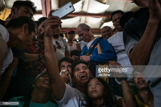 Filipino fans watch and cheer from a cell phone the boxing fight of Manny Pacquio and Adrien Broner on January 20 2019 in Pacquiaos hometown of...