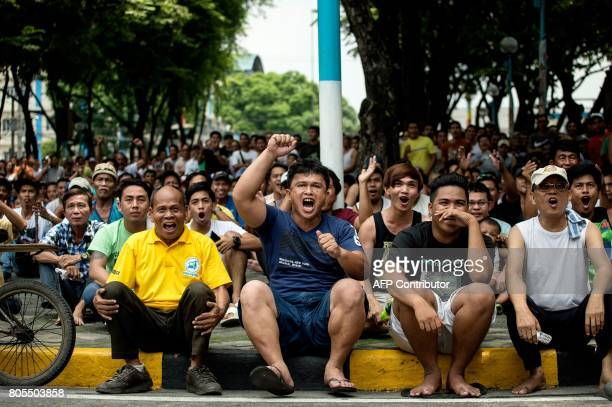 Filipino fans watch the World Boxing Organisation welterweight boxing match between Manny Pacquiao of the Philippines and challenger Jeff Horn of...