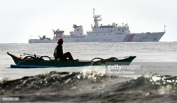 Filipino fisherman operates around Scarborough Shoal while a Chinese Coast Guard ship on December 13, 2016 in Scarborough Shoal, South China Sea....
