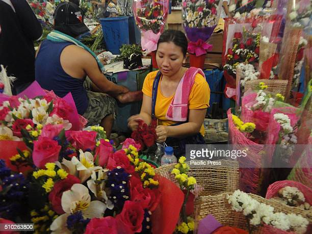 Filipino florist arranges flowers at the Dangwa flower market in Manila Philippines on Valentine's Day Valentines Day is celebrated on February 14...
