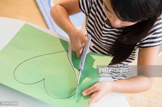 Filipino girl cutting heart shape out of paper