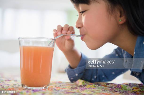 Filipino girl drinking juice on table