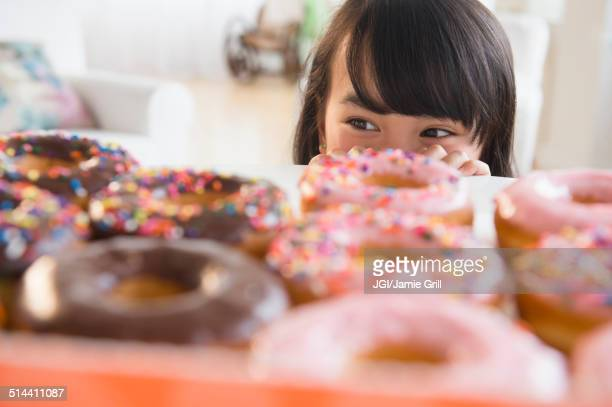 Filipino girl peering at donuts on table