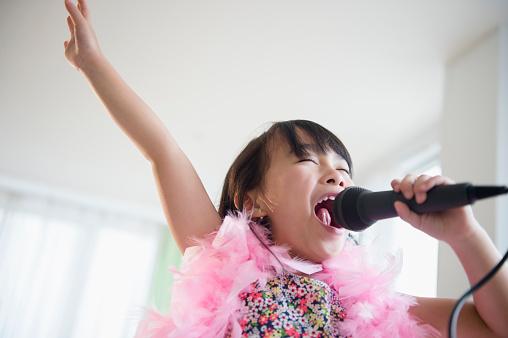 Filipino girl singing karaoke in living room - gettyimageskorea