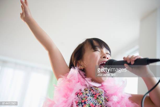 filipino girl singing karaoke in living room - singing stock pictures, royalty-free photos & images