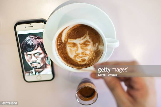 Filipino graphic artist Zach Yonzon sketches the face of Manny Pacquiao in the milk foam of a cup of coffee in a cafe on April 23 2015 in Quezon City...