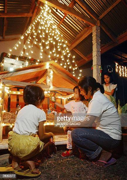Filipino housewife Emma Perlano tells the story of Christmas to her two daughters Hanna and Eileen in front of a mini replica of the barn house...