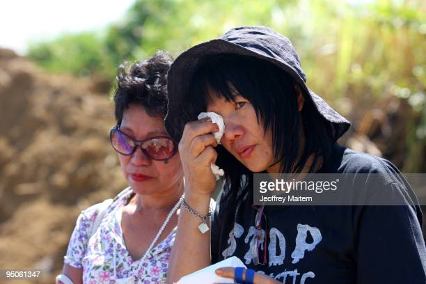 Filipino journalist wipes tears away as others offer flowers prayers and light candles at the site where 57 people including many journalists were...