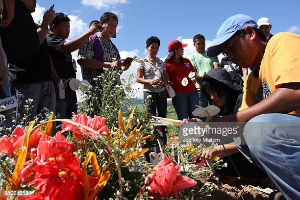 Filipino journalists offer flowers prayers and light candles at the site where 57 people including many journalists were massacred on November 23 by...
