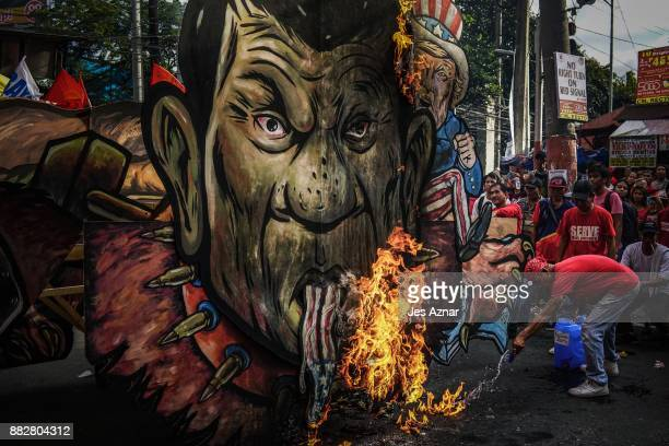 Filipino leftist protesters burn an image of President Rodrigo Duterte on November 30 2017 in Manila Philippines After announcing his withdrawal from...