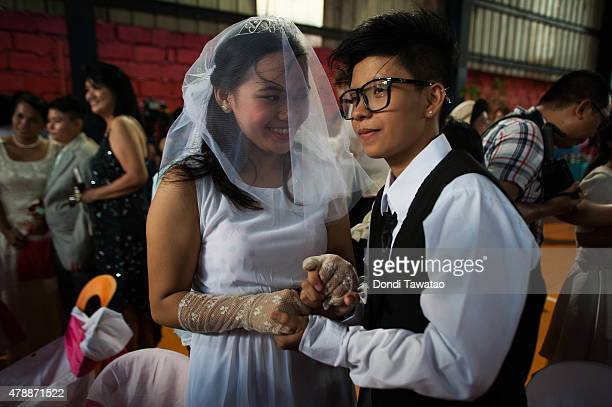 Filipino LGBT couple exchange 'Rite of Holy Union' vows during mass 'wedding rites' on June 28 2015 in Manila Philippines A small Christian...