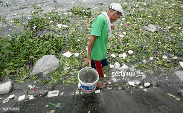 Filipino man carries a bucket of seawater along the coast of Manila Bay. According to the Bureau of Fisheries and Aquatic Resources , the prevailing...