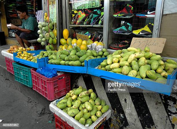 Filipino man eats an afternoon snack beside a ripe and unripe mangoes being sold along EDSA highway State weather forecasters said that warmer days...