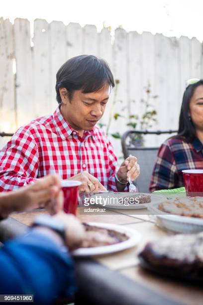 filipino man enjoys steak at outdoor dinner - filipino family dinner stock pictures, royalty-free photos & images