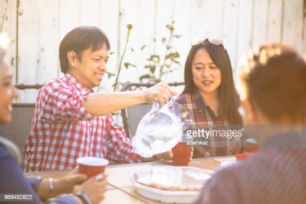 filipino man pouring water at dinner - daily life in philippines stock pictures, royalty-free photos & images