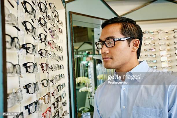 Filipino man trying on glasses at optometrist