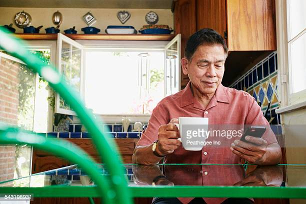 filipino man using cell phone in kitchen - filipino - fotografias e filmes do acervo