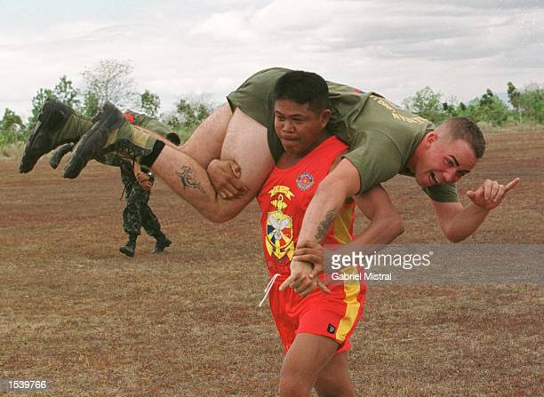 Filipino Marine carries a U.S. Marine during a Fireman's drill exercise inside the Philippine Army camp of Fort Magsaysay May 4, 2002 located north...