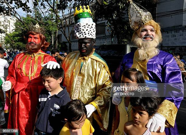 Filipino men dressed in costumes as the Three Kings distribute candies to children on the streets of Manila on January 3 2010 AFP PHOTO / JAY DIRECTO