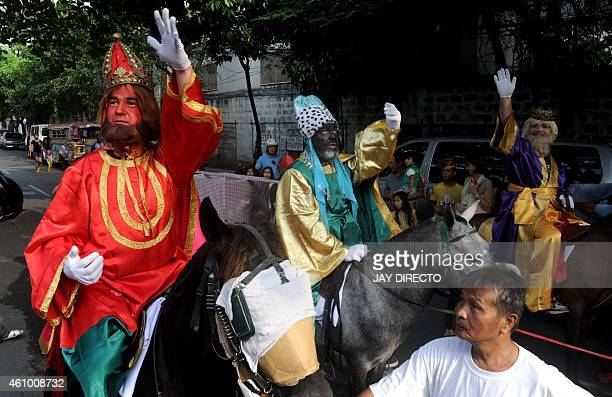 Filipino men dressed in costumes as the Three Kings parade along a street as they throw candy to children in Manila on January 4 2015 The feast day...