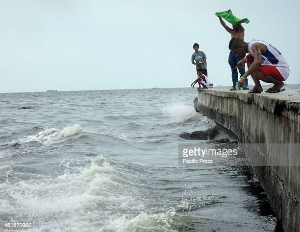 Filipino men fish along the Manila Bay shore in Navotas City.
