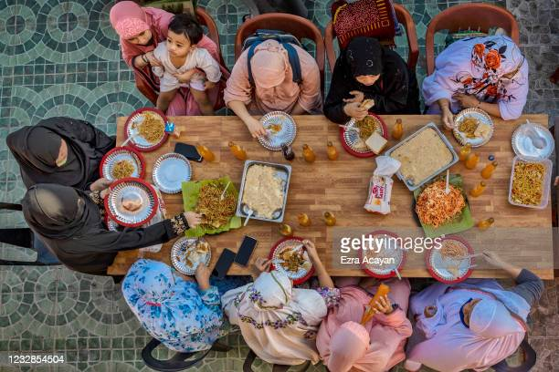 Filipino Muslims eat a meal together as they celebrate Eid al-Fitr at the Garden Mosque on May 13, 2021 in Taguig, Metro Manila, Philippines. Eid...