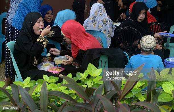Filipino Muslims eat lunch as they gather to celebrate the end of Eid AlAdha at a park in suburban Manila on October 6 2014Muslims across the world...