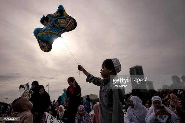 Filipino Muslims flock to a public park to attend prayers and celebrate Eid alFitr on June 15 2018 in Manila Philippines Muslims around the world...